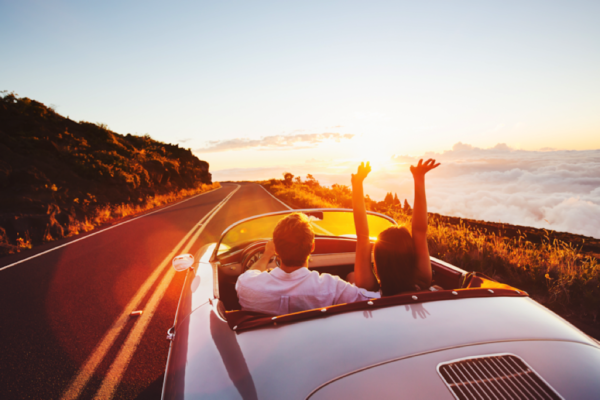 Image of couple driving in convertible.